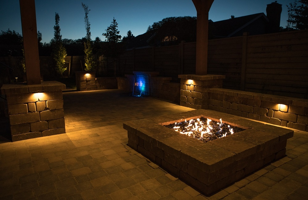 patio with landscape lighting and fire pit